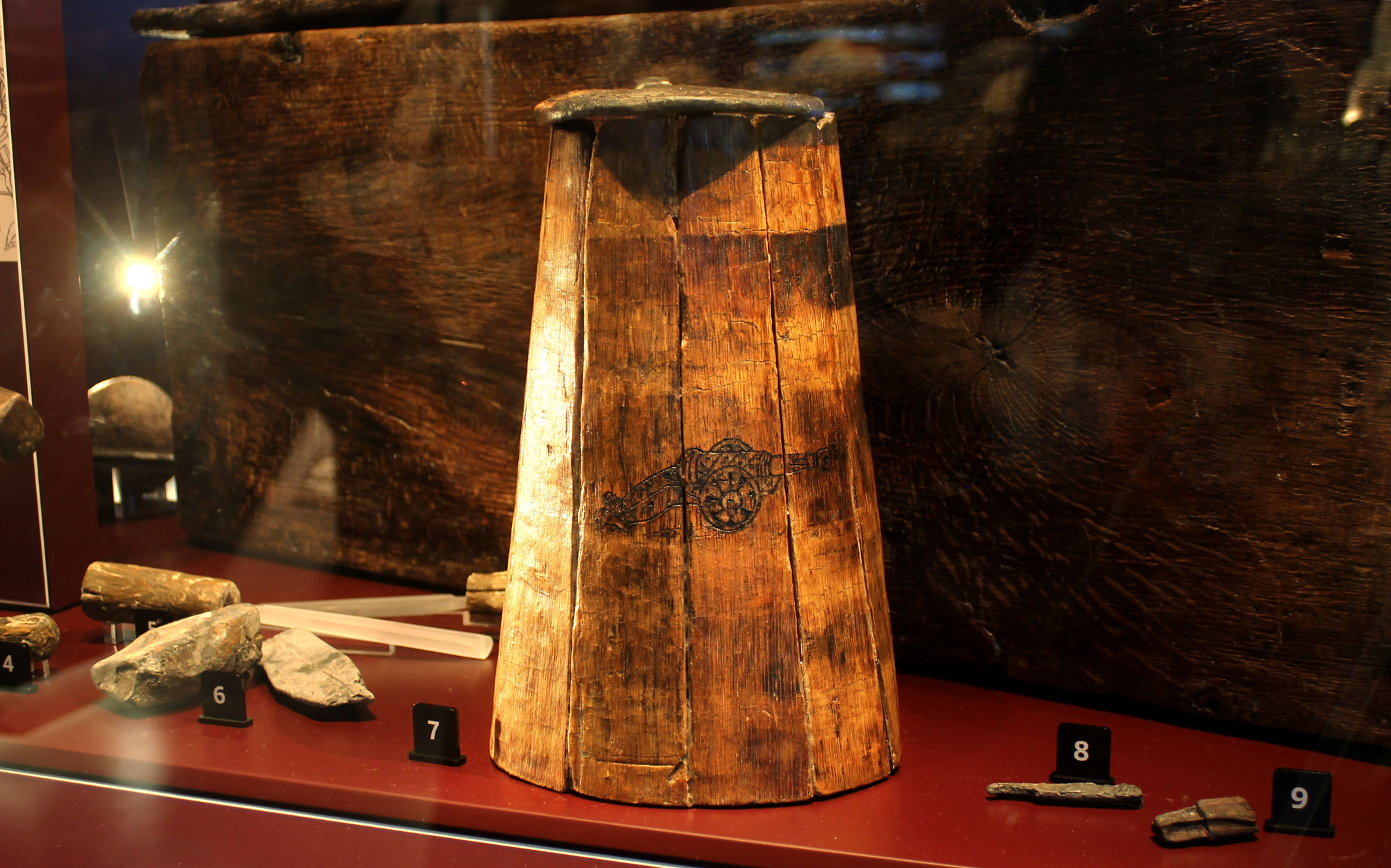 a photo of a large wooden flagon in a display case