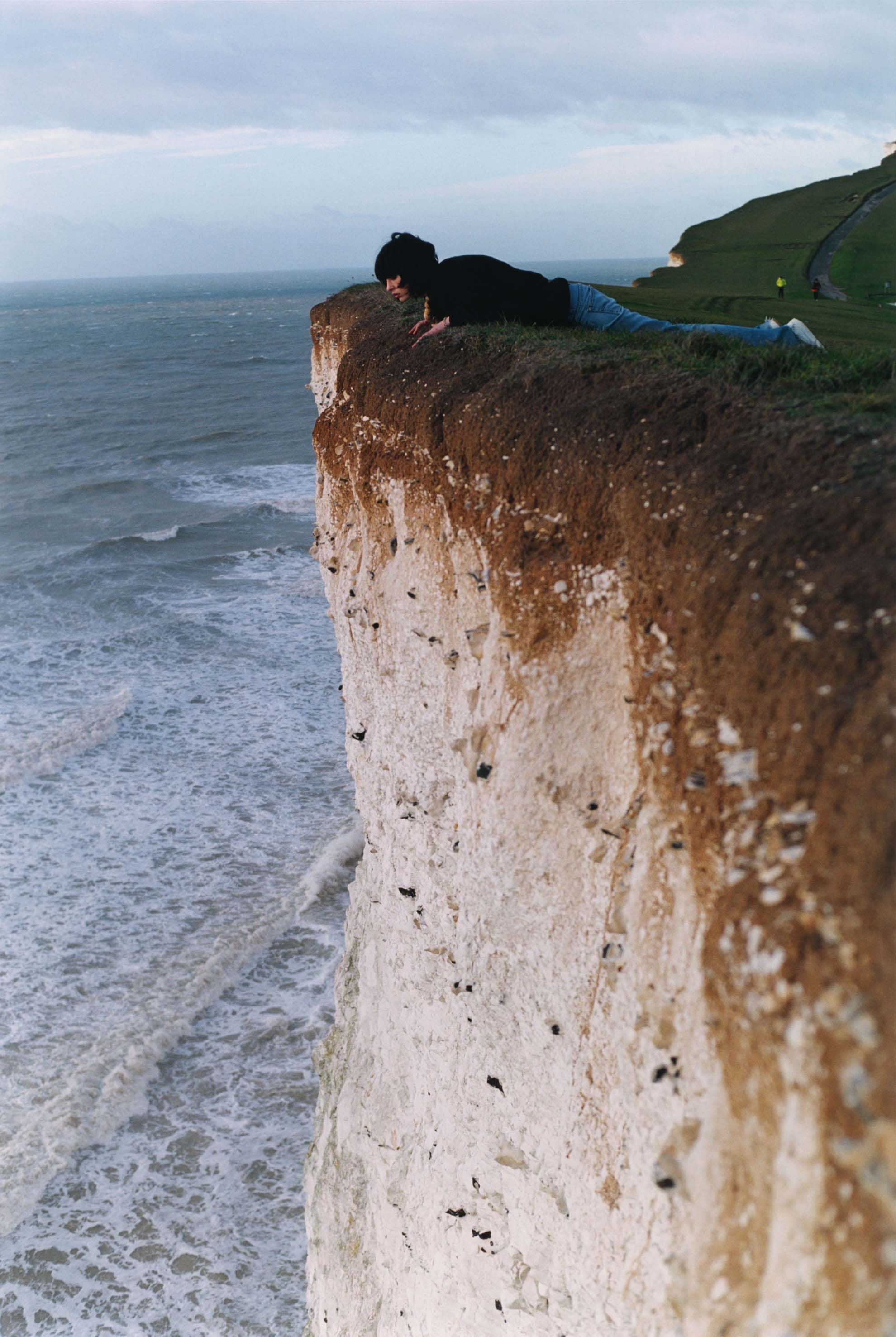 a photo of a woman lying on the top of a cliff peering over the edge