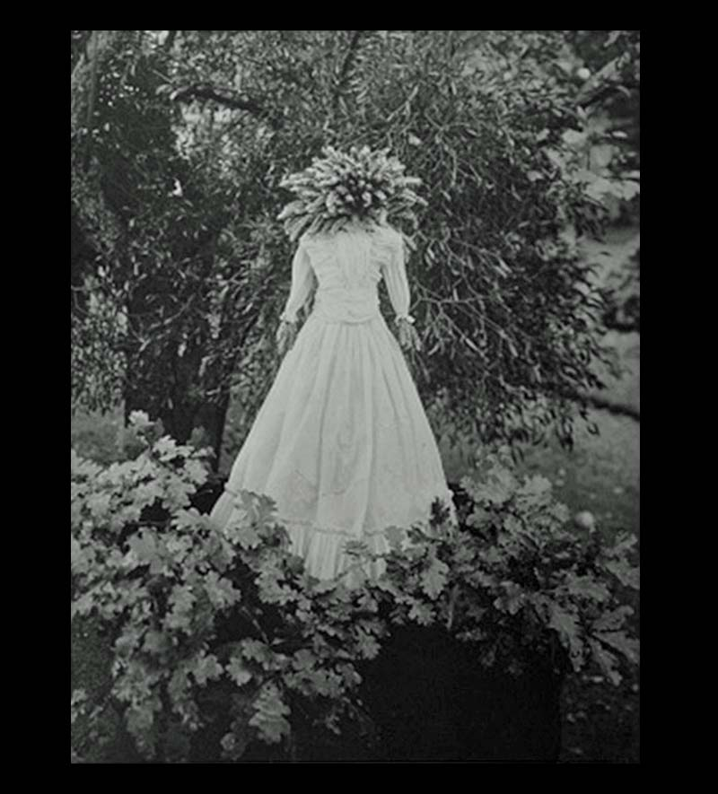 a black and white photo of a corn dolly in a dress