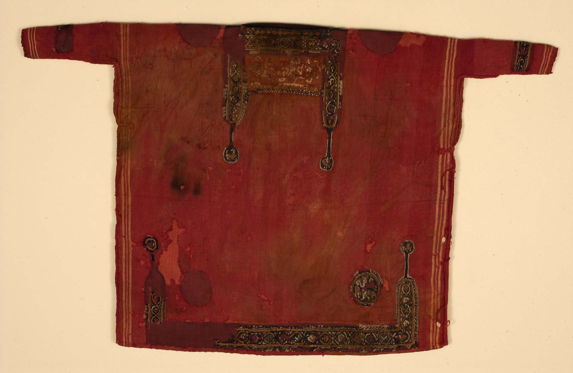 a photo of a tunic in red with gold brocade decoration