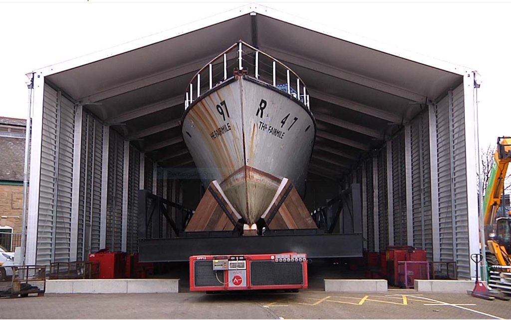 a photo of the hull of a large boat potruding from the entrance of a corrugated shed
