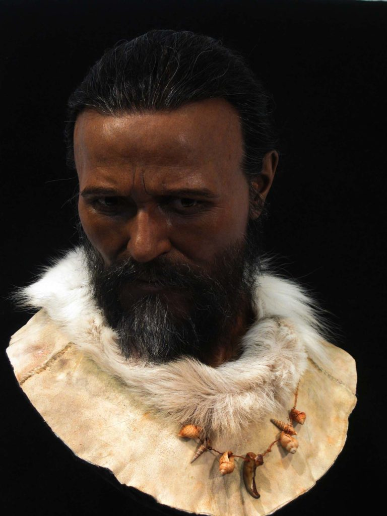a photo of a recreation of a bearded man with dark skin and goatskin tunic