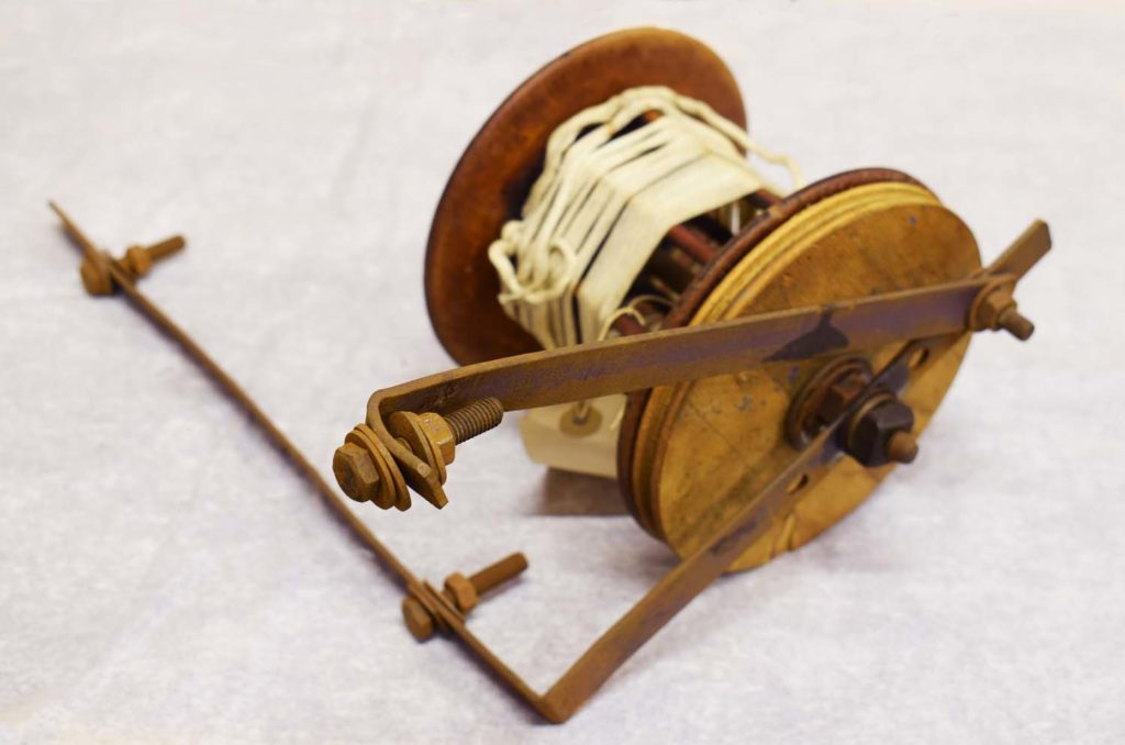a photo of a reel like object with spindle and metal bars attached