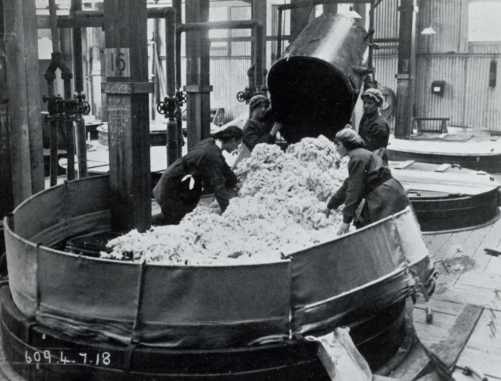 a photo of a group of women loading white stuff into a large vat in a factory