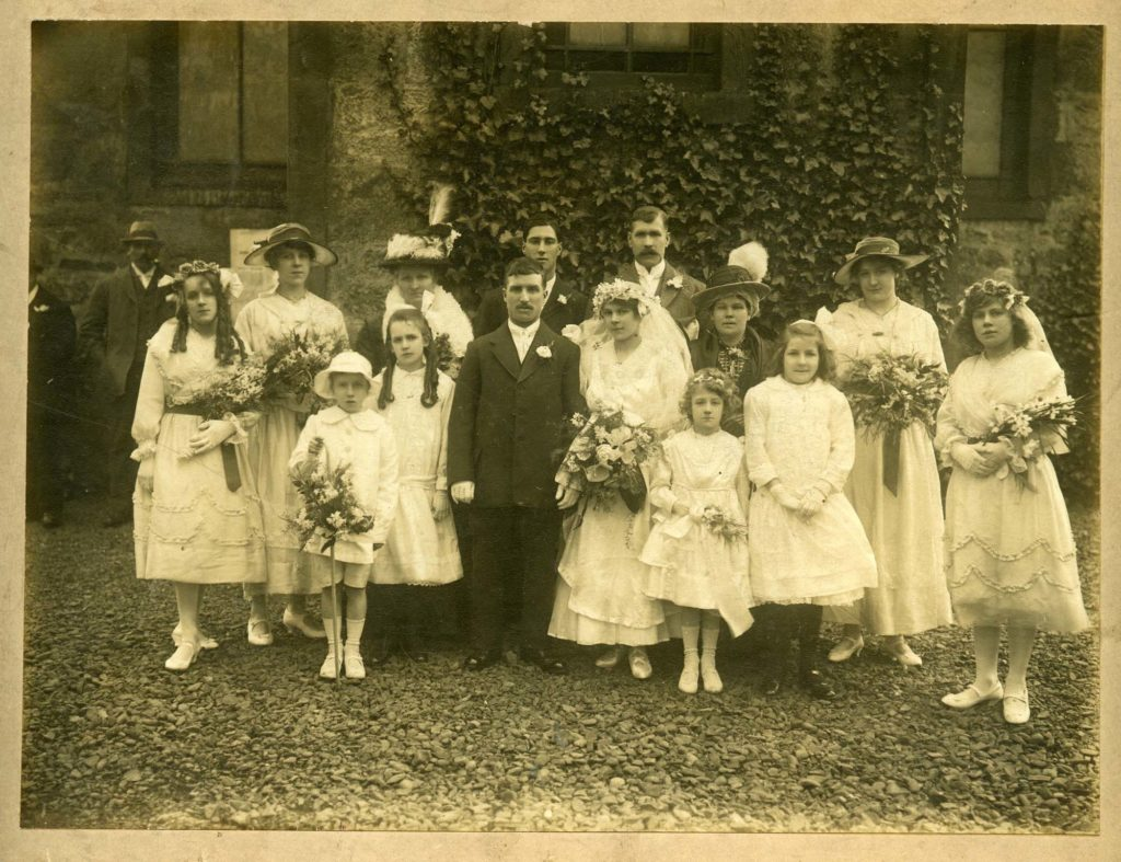 a late Edwardian group wedding photo showing bride, groom, best man, bridesmaids and other family members