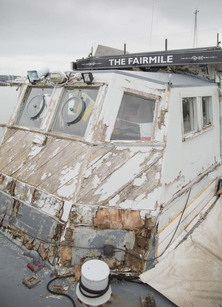 a photo of a ships' deck cabin with peeling paint and exposed wood