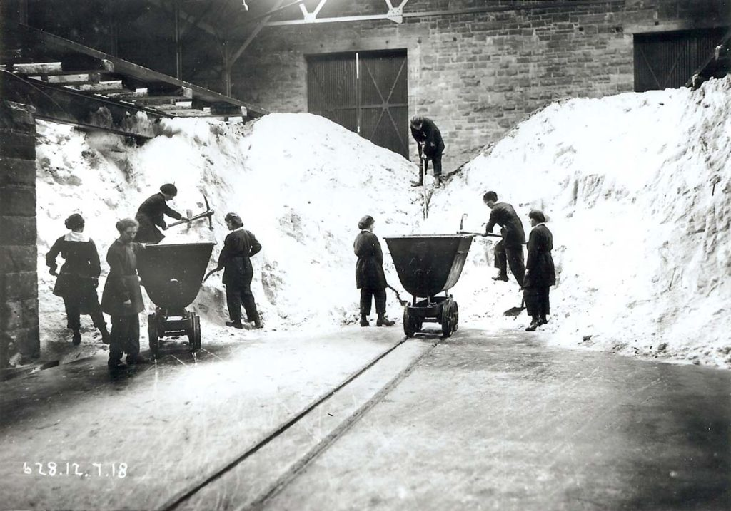 a photo of a small group of women shovelliing from large piles of a white substance in a factory