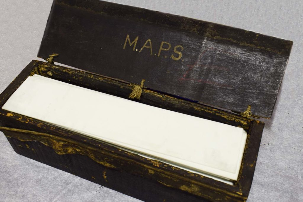 a photo of an oblong wooden box with open lid and sheets of glass inside