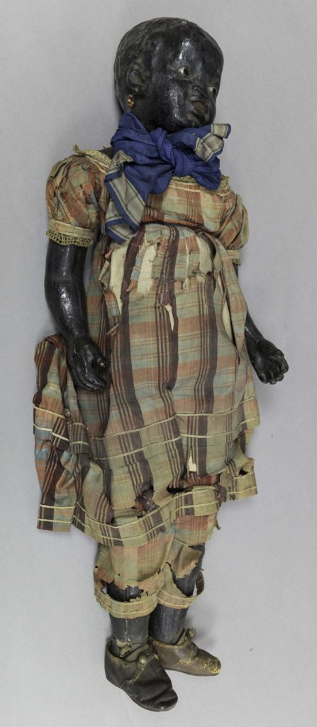 a photo of a large black doll in ragged plaid clothing