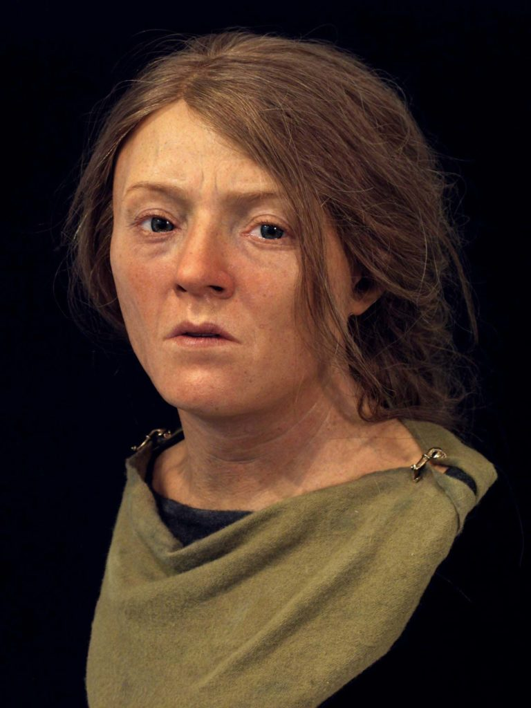 a photo of a recreated woman with ginger sandy hair and a green tunic