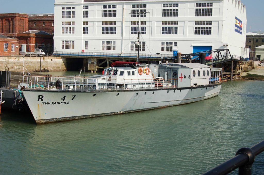 a photo of a long sleek grey shop moored at a dockside