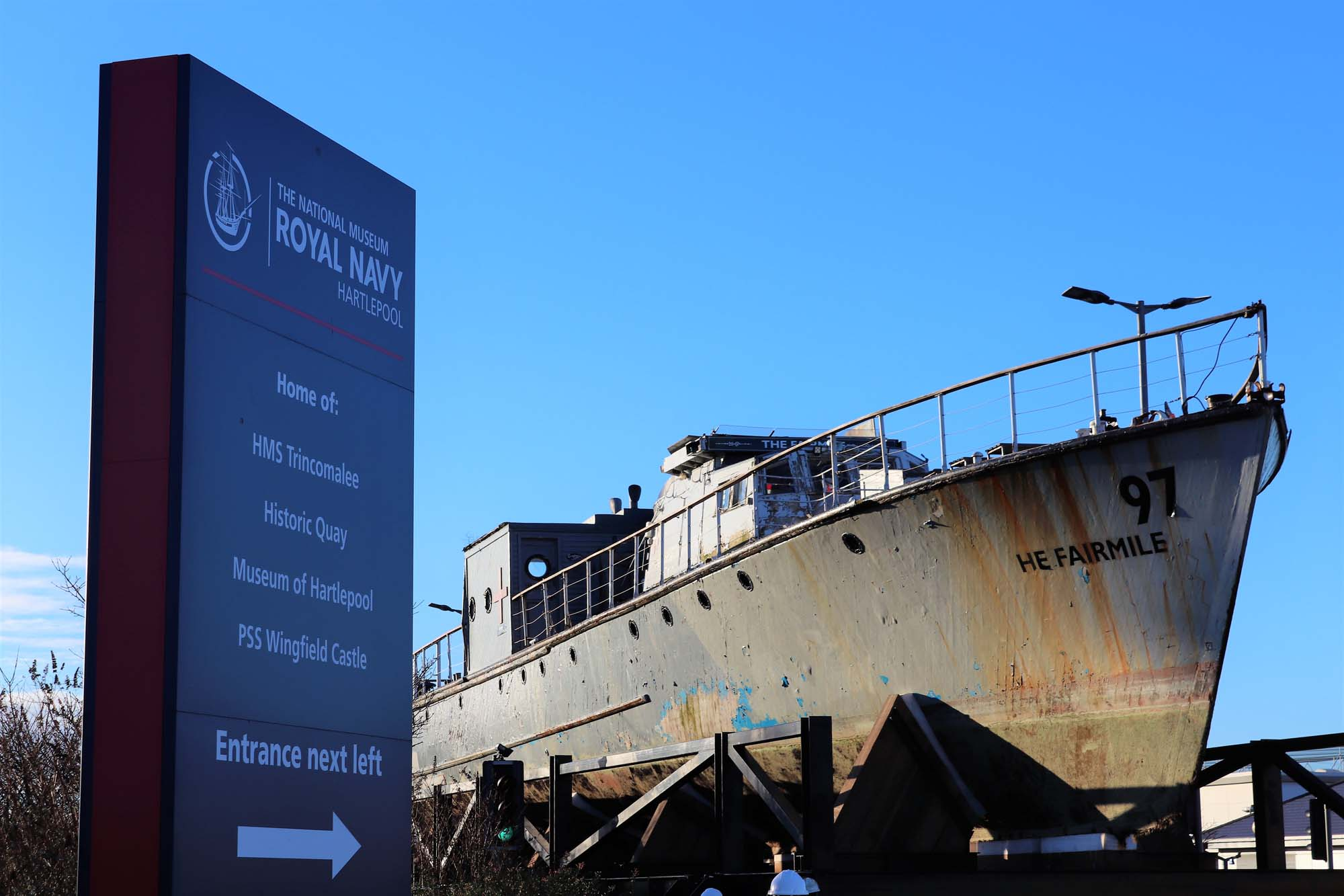 a photo of a the hull of a large grey painted boat photographed against a winter blue sky
