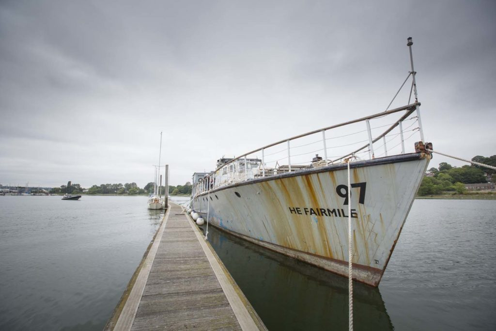 a photo of an old weathered boat in grey berthed next to a jetty
