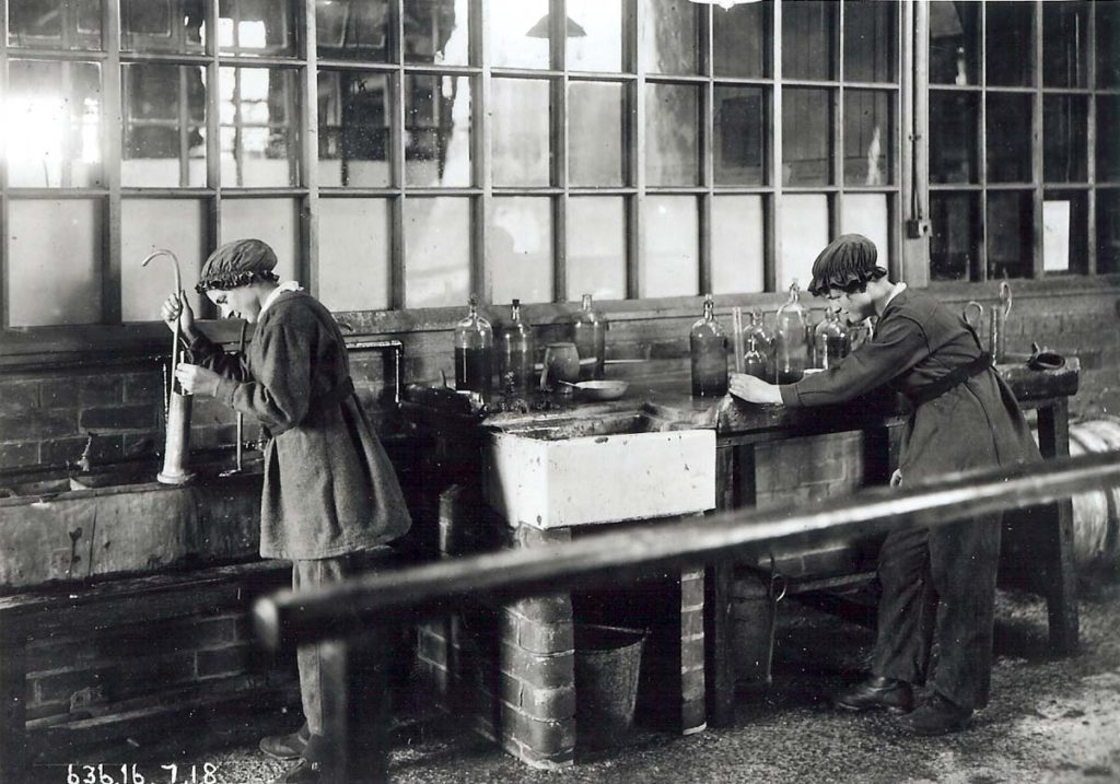 a photo of two women working with a series of glass cases on a workshop bench