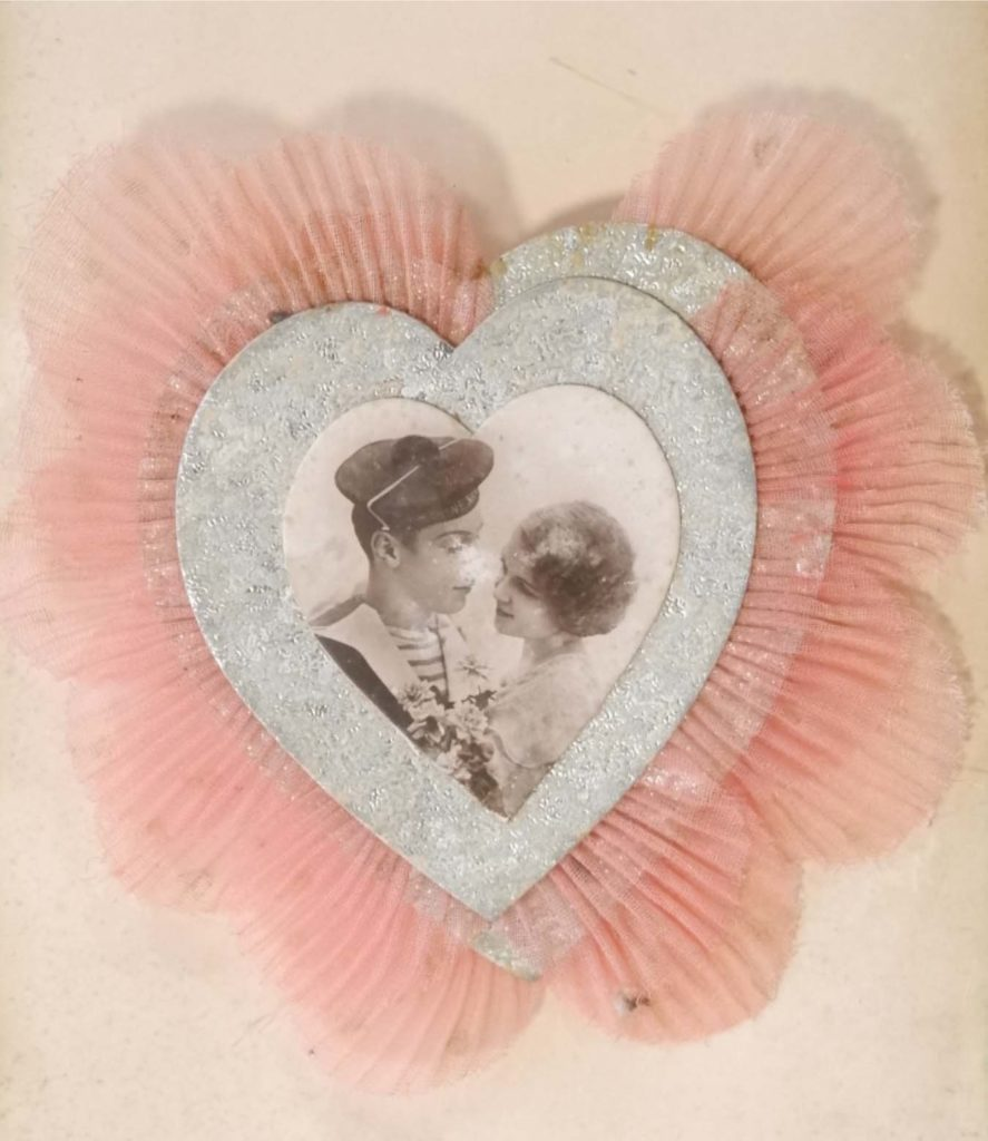 a card with a heart shape with a picture of a sailor and young woman at its centre