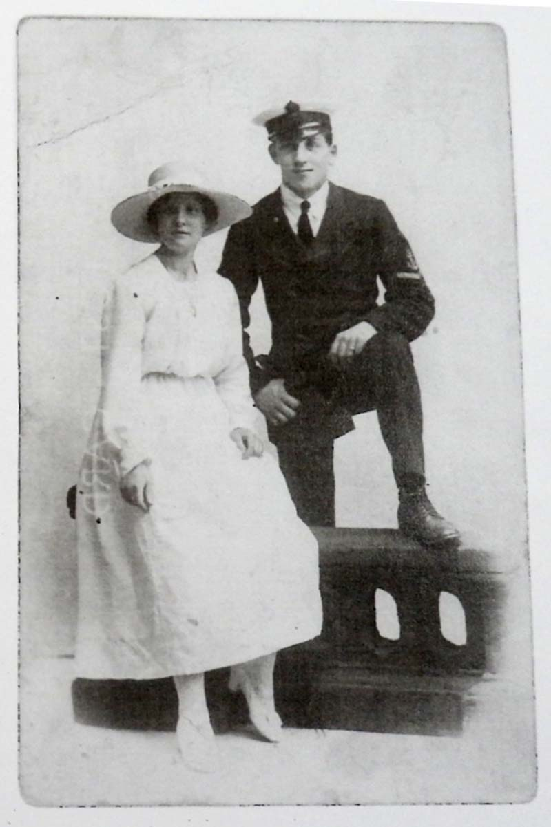 a photo of a sailor and wife in wite gown and wide brimmed hat