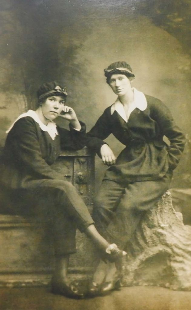 a studio portrait of two women in munitions worker clothing