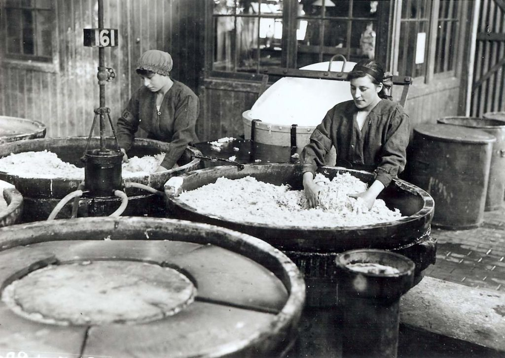 a photo of two women mixing a white substance in large vats by hand