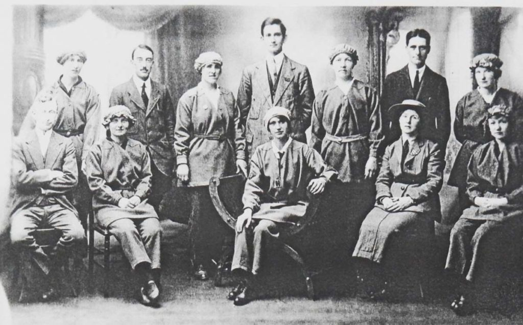 a photo of a large group of woman in munitions clothing and men in morning suits