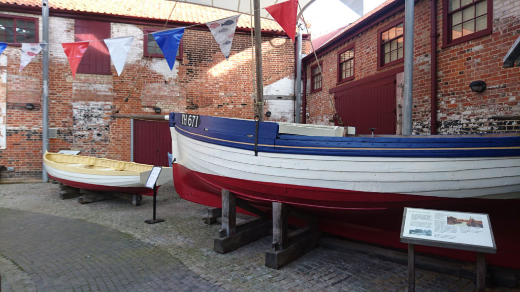 photograph of exterior of red brick building with two small historic boats outside