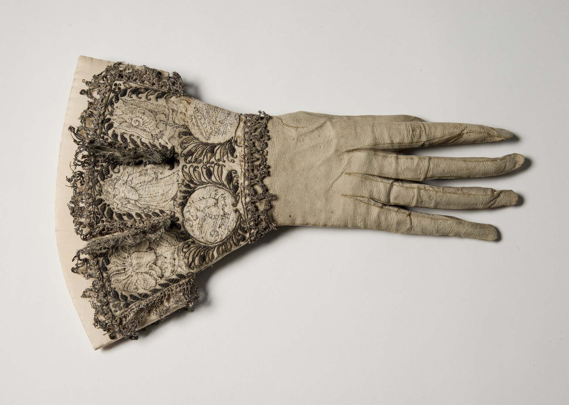 a heavily cuffed and embroidered leather glove