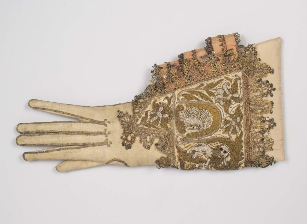 a photo of a cream glove with heavily embroidered cuff