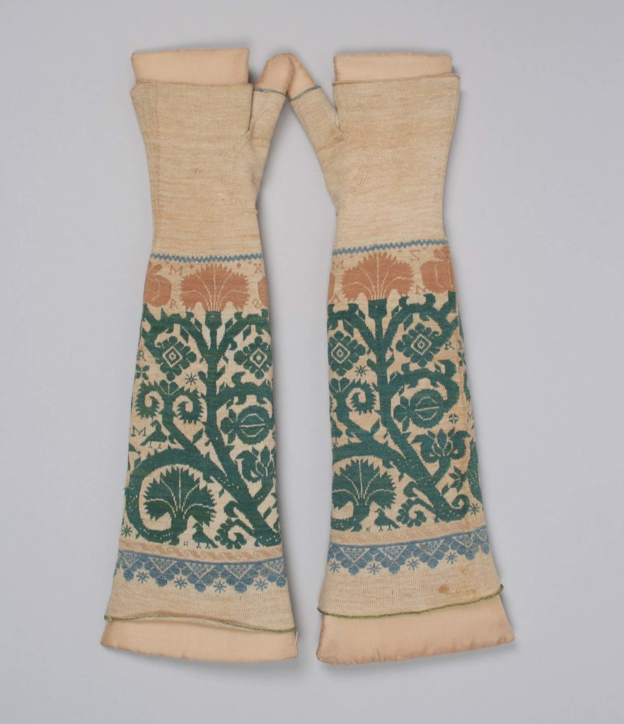 a pair of long elbow length fingerless mittens made of woll with green floral decoration