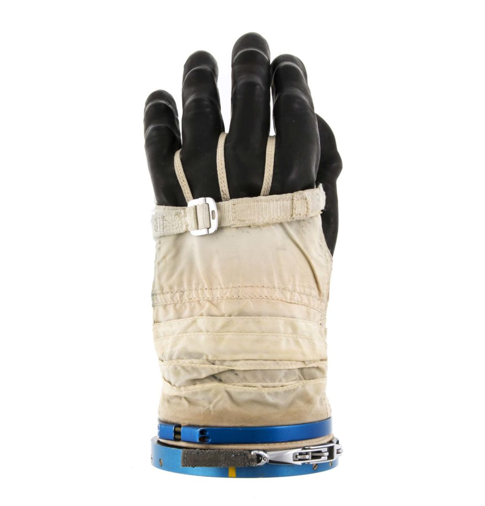 a photo of white glove with heavy black rubber fingers and a metallic blue cuff