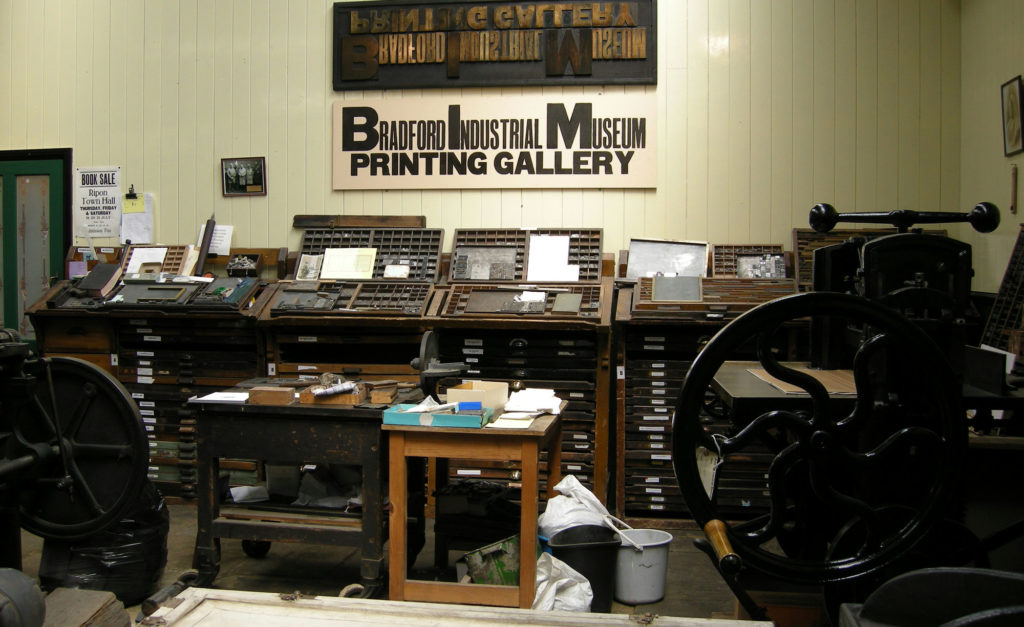 photograph of museum display showing printing materials and tools, including chests of type