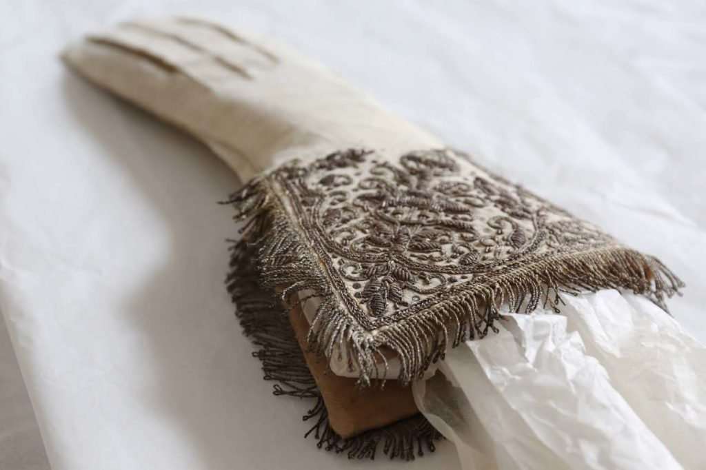 a photo of an ornately decorated white gauntlet glove