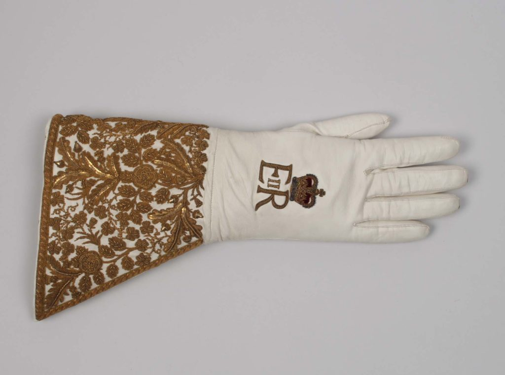 a photo of gold decorated gauntlet glove with the ERII cypher on it