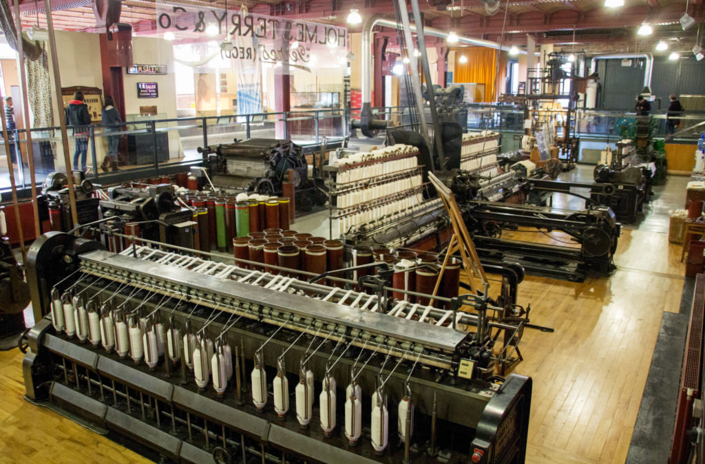 photograph of interior of museum with large cooton industry machines on display