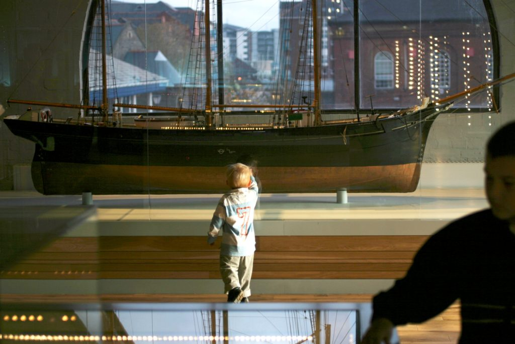 photograph of young child walking towards a boat model on display in a museum