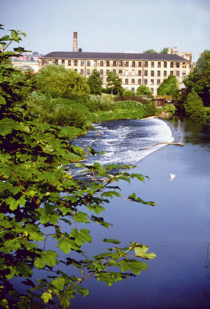 photograph of large mill building with weir in front