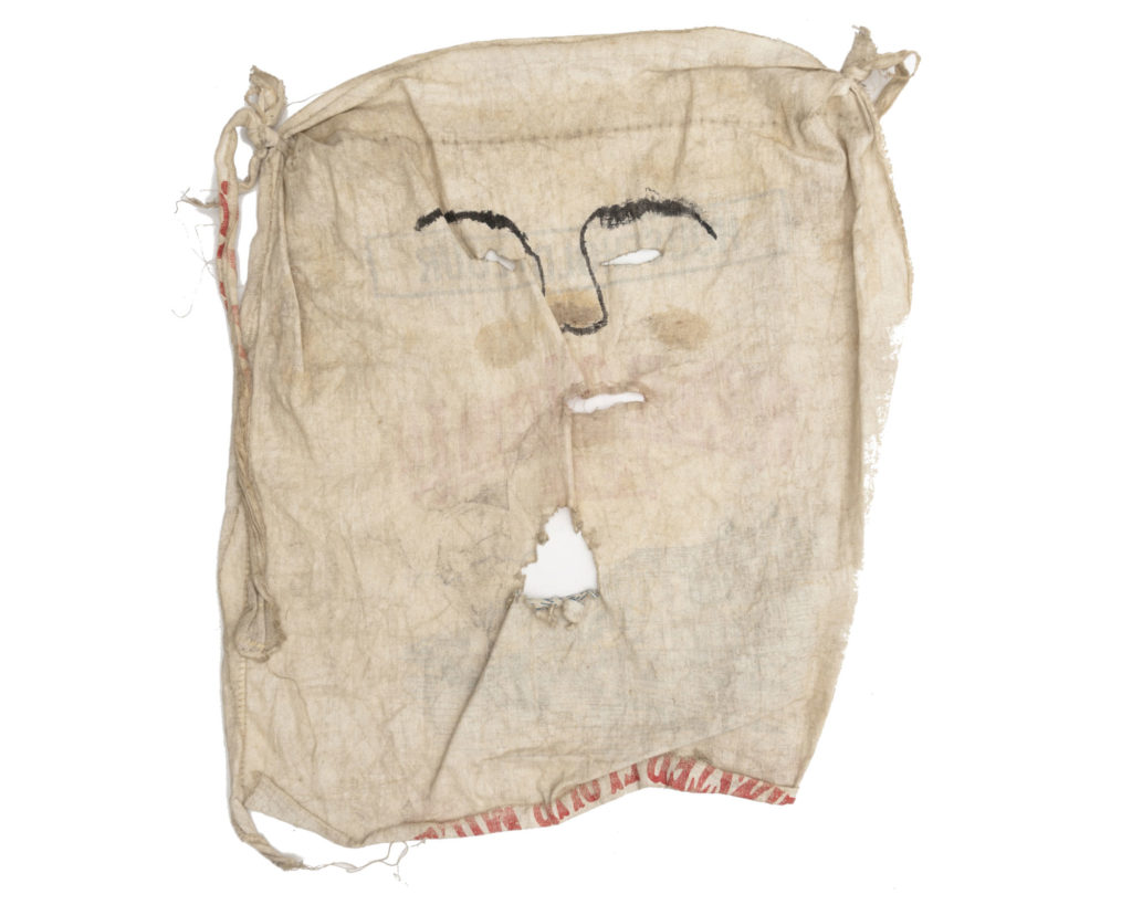 mask made from piece of flour sack with simple face drawn on and holes for eyes, nose and mouth