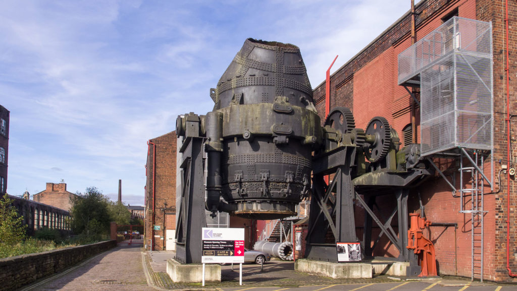 photograph of exterior of building with large piece of iron industrial machinery outside