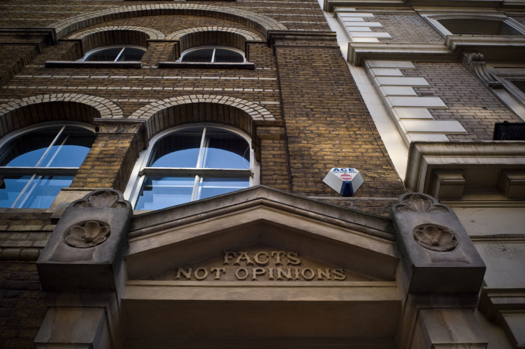 photograph of exterior of building, focusing on a decorative stone lintel reading 'facts not opinions'