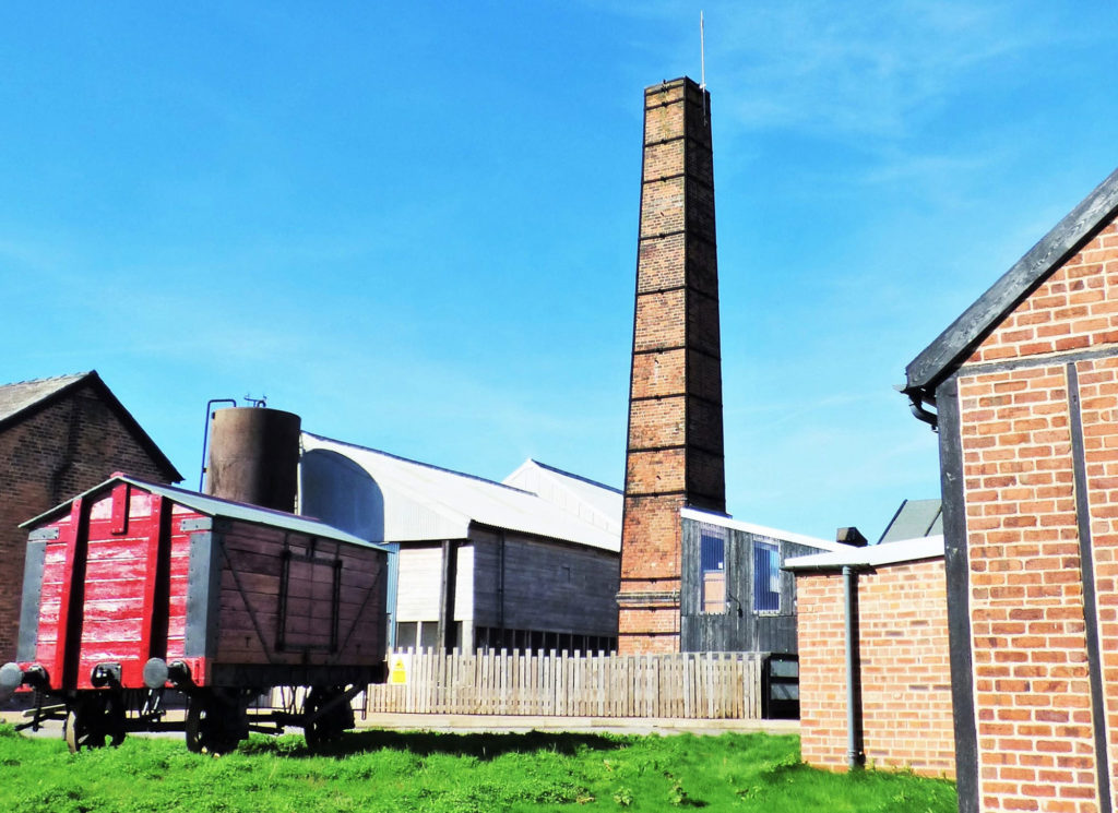 photograph of exterior of industrial site, with red wooden cart and large brick chimney