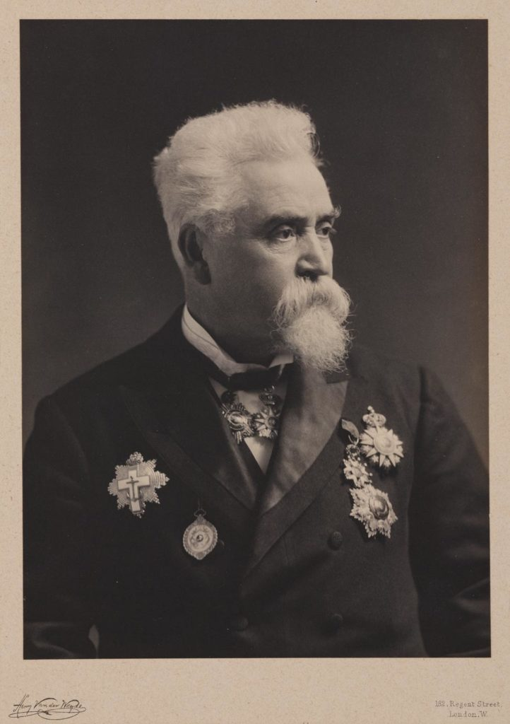 photograph of man with white hair and beard wearing dark coat and medals
