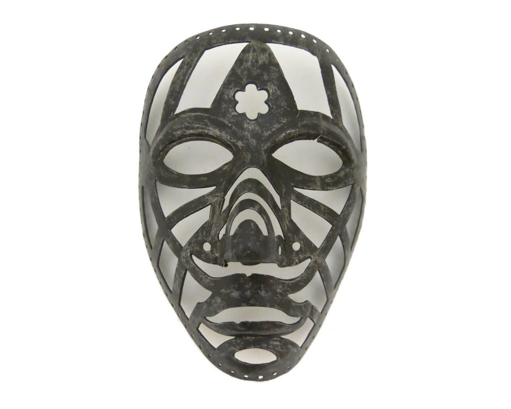 an open ironwork mask with holes for the eyes and mouth, and a flower motif on the forehead