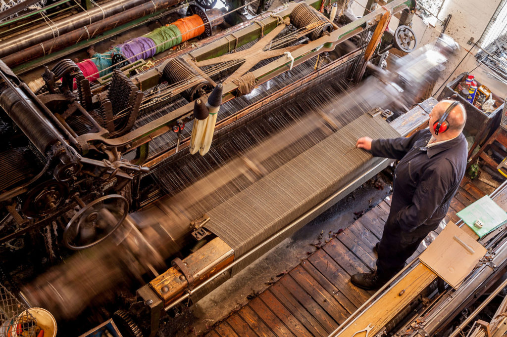 photograph of man working at a large weaving loom