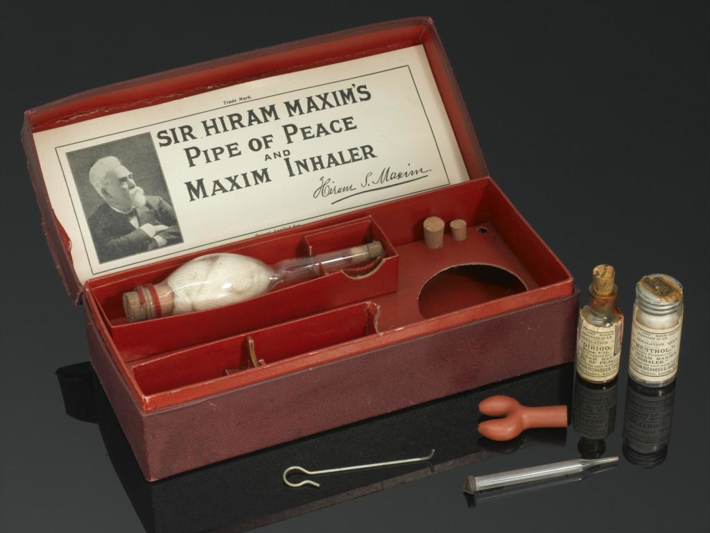 photograph of red box containing glass inhaler. there are spaces for a larger inhaler and outside of the box sits two small glass bottles and some small tools