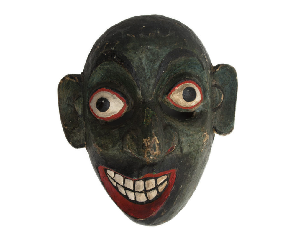 photograph of wooden mask showing dark green face with wide eyes and lopsided mouth with large red lips