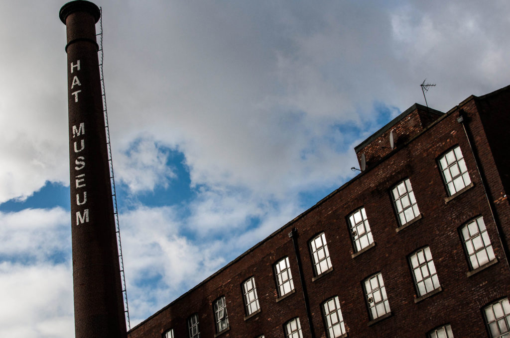 photograph of exterior of large brick building with tall chimney reading 'hat museum'