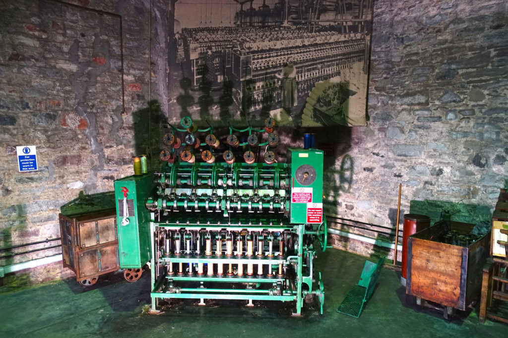 photograph of green industrial textile-manufacturing machine against a stone wall with black and white archive photograph of machines in use on the wall