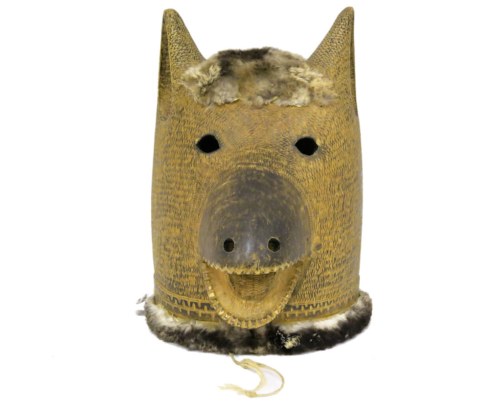 large wooden mask in the shape of a bear, with open mouth with string attached, pointy ears and two small round holes for eyes. The mask is lined and topped with fur and in painted in a yellow/gold colour
