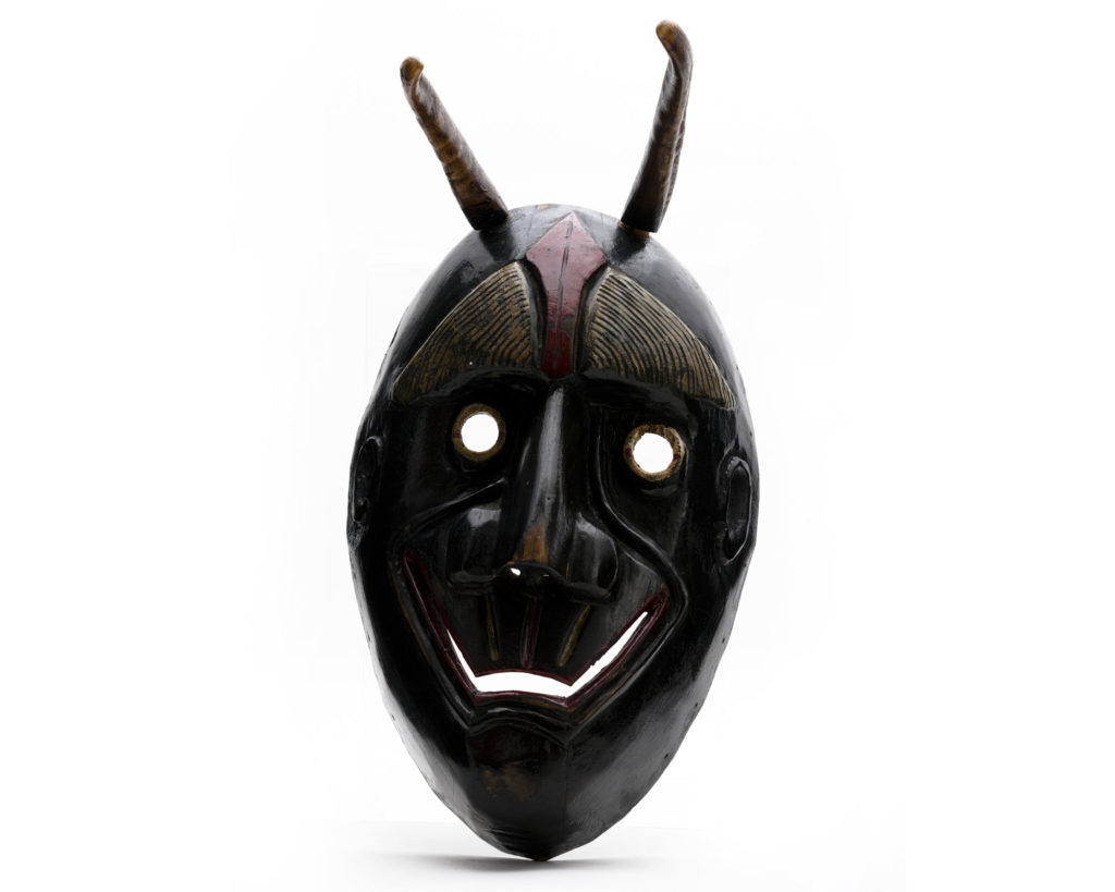 wooden mask showing very dark oval face with angular mouth and circular eyes. There are two horns on top