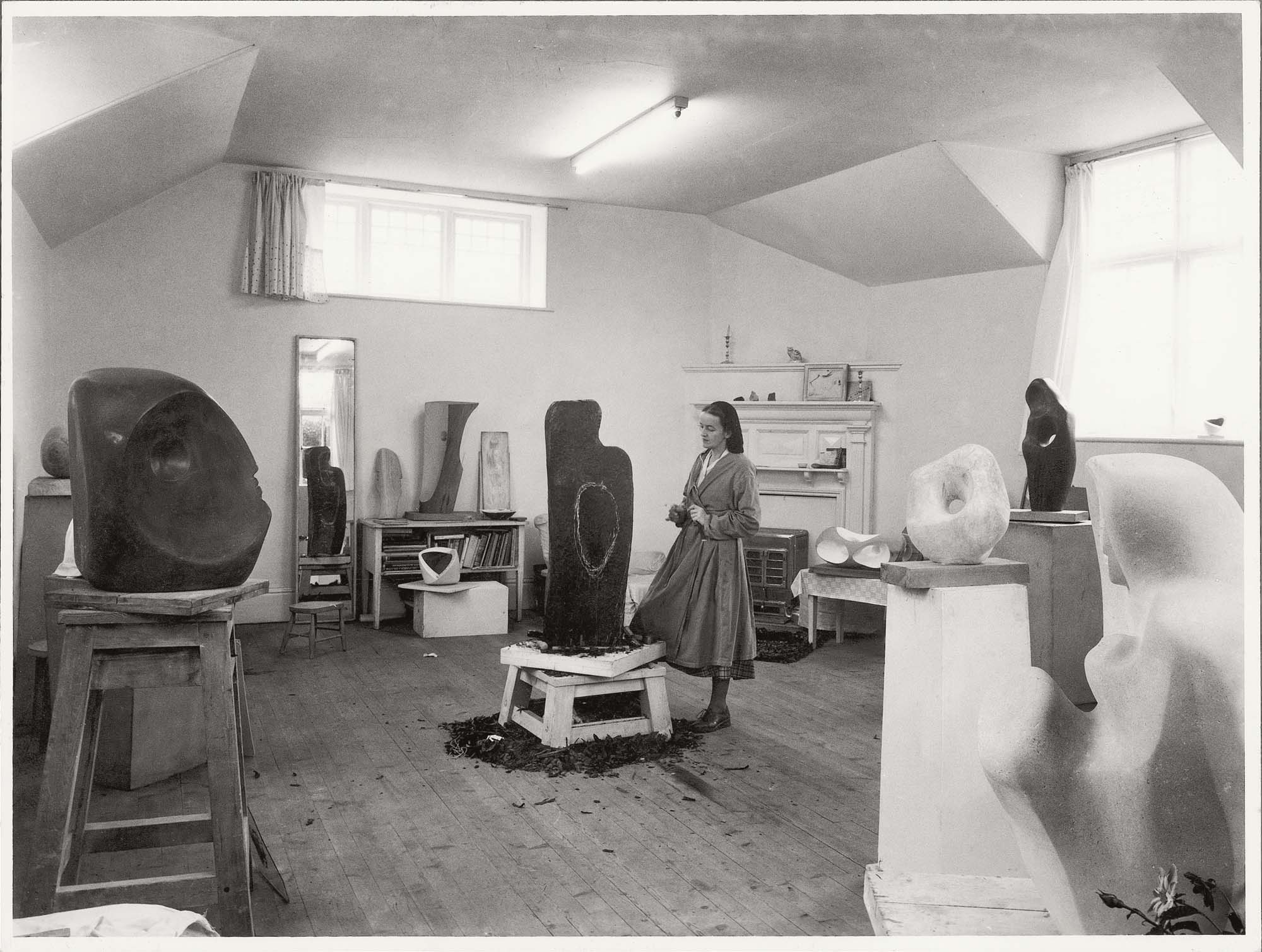 a black and white photo of a woman sculpting a large block in a light and airy studio