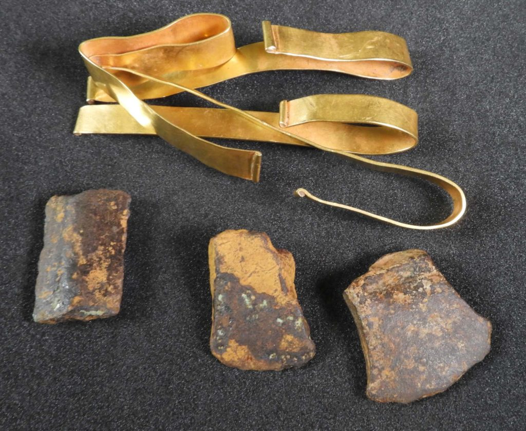 A photo of a three gold bracelets and three exe fragments