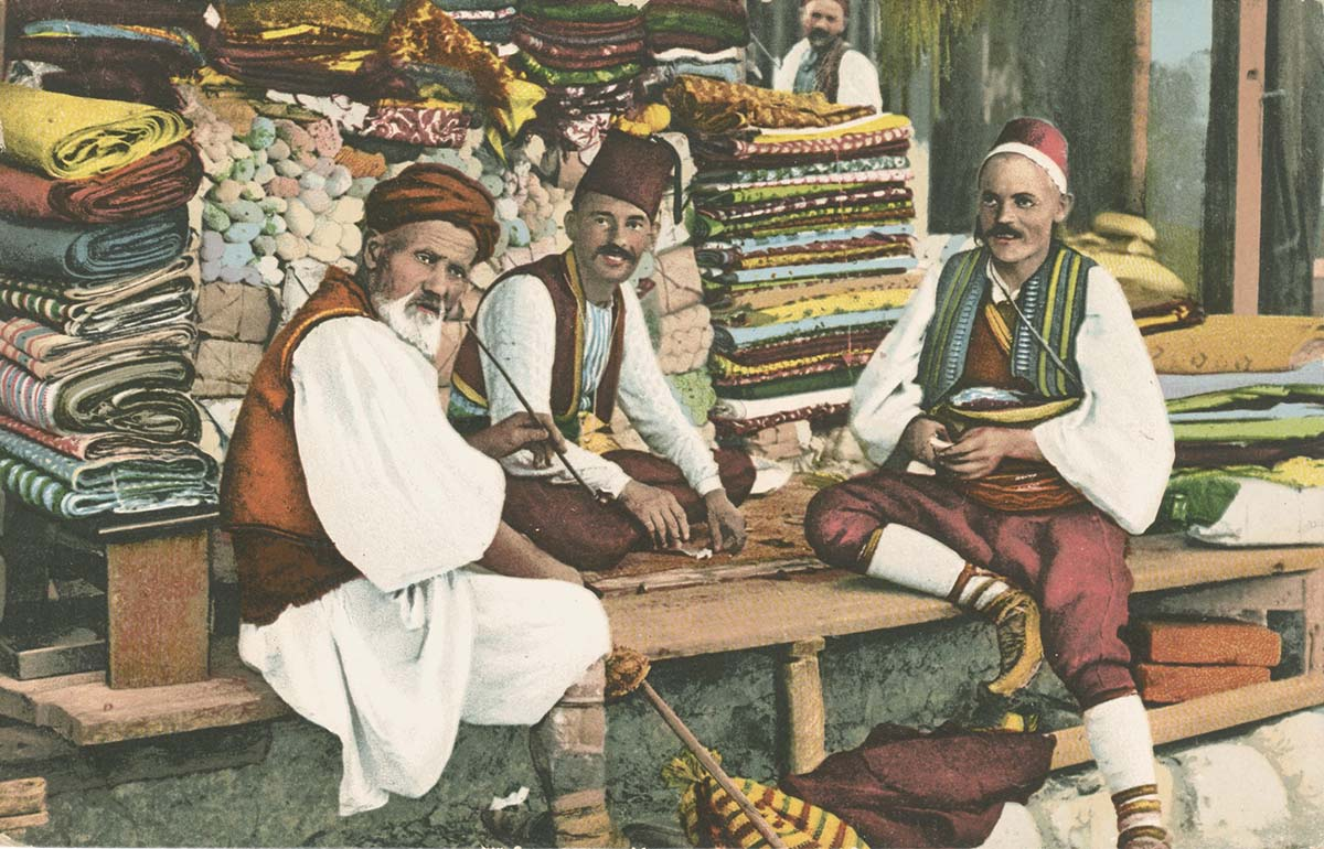 a colour postcard of three men sitting on a cot in a bazaar waring knee length breeches, waistcoats, billowing shirts and fezes and turbans
